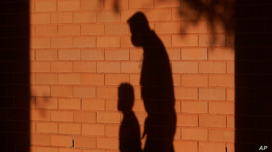 FILE - In this Friday, Oct. 9, 2020 file photo, the shadows of a school employee escorting a student are cast on the wall as…