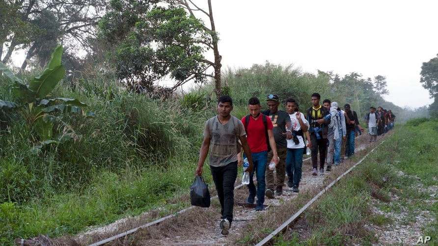 Migrants walk on train tracks on their journey from Central America to the U.S. border., in Palenque, Chiapas state, Mexico,…