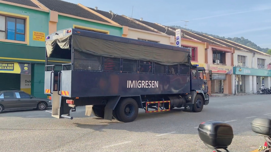 In this image taken from a video, an immigration truck with unidentified people onboard is driven on a road that leads to Lumut Naval Base Tuesday, Feb. 23, 2021 in Lumut, Malaysia.