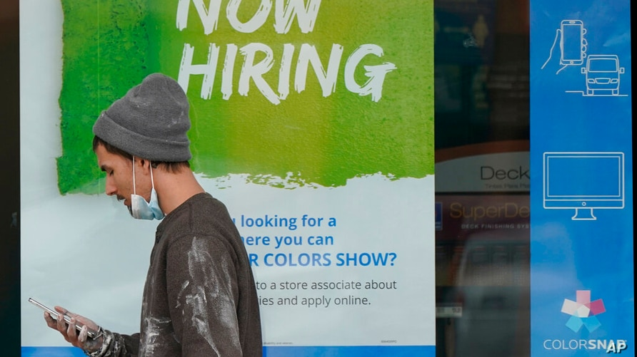 "A man walks past a ""Now Hiring"" sign on a window at Sherwin Williams store, Friday, Feb. 26, 2021, in Woodmere Village, Ohio…"