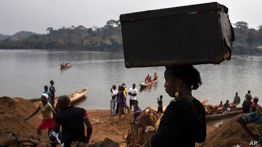 An unidentified woman carries her belongings on her head after crossing the Mbomou river back into Bangassou, Central African…