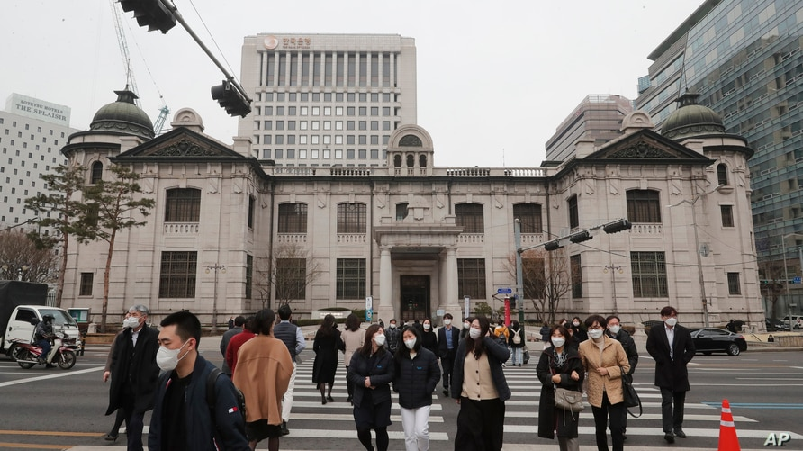 People wearing face masks walk by the headquarters of the Bank of Korea in Seoul, South Korea, Thursday, March 4, 2021. South…