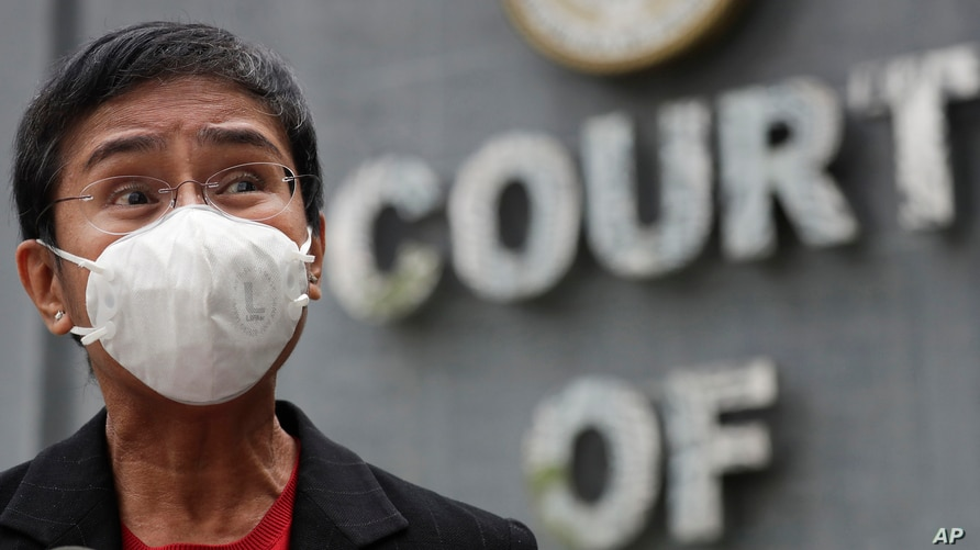 Rappler CEO and Executive Editor Maria Ressa, wearing a face mask to prevent the spread of the coronavirus, talks to reporters…