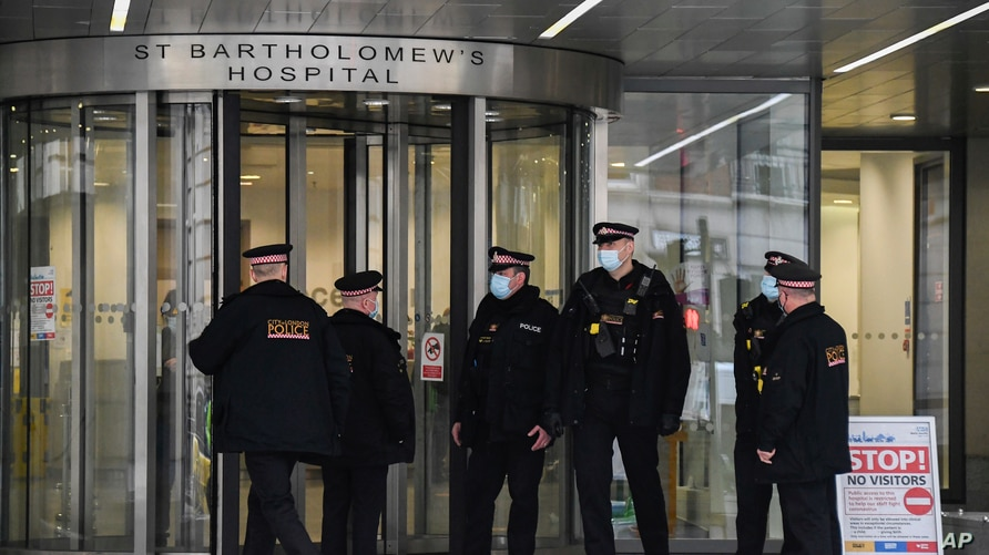 Police officers stand outside the main entrance of the St Bartholomew's Hospital where Britain's Prince Philip is being treated.