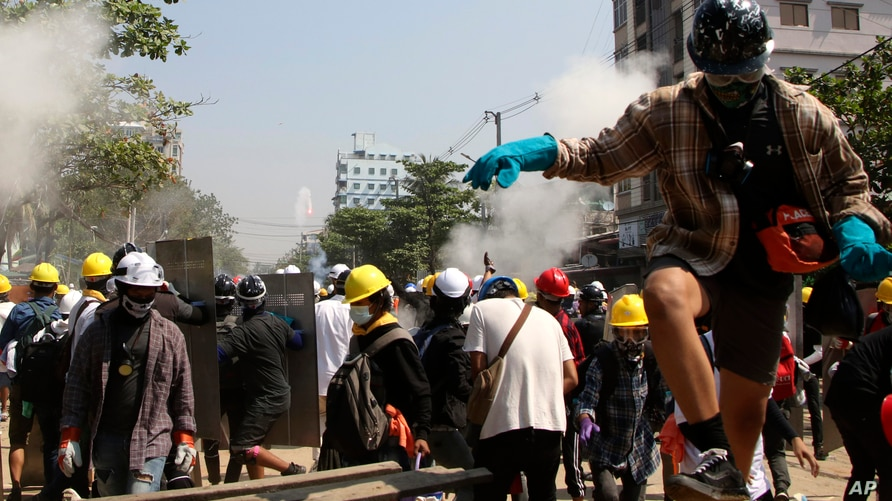 Protesters are dispersed as riot police fired tear gas behind a makeshift barricade in Yangon, Myanmar, March 7, 2021.