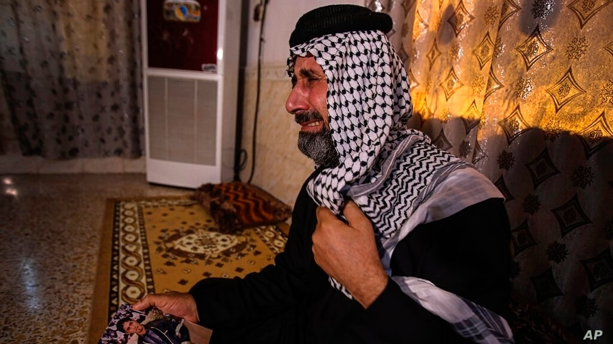 FILE - In this July 29, 2020 file photo, Jasb Hattab Aboud, father of the kidnapped protester Ali Jasb, cries as he holds his…
