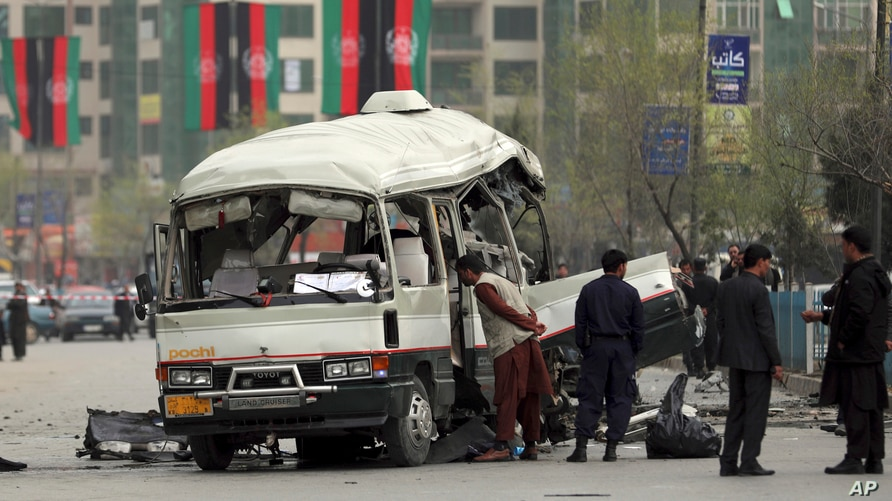 Security personnel inspect the site of a bomb attack in Kabul, Afghanistan, Monday, March 15, 2021. A bomb targeting a minibus…