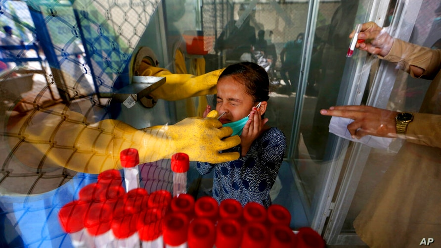 A young girl reacts while having a nasal swab sample taken by a health worker at a COVID-19 testing facility in a hospital in…