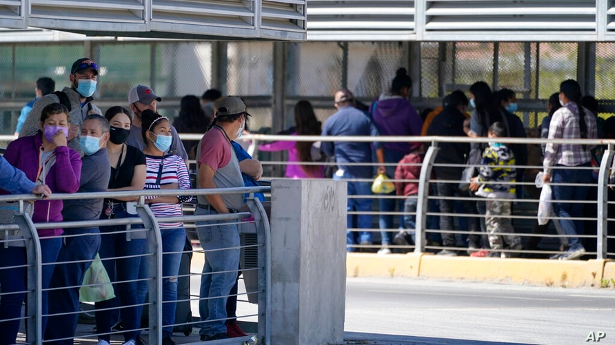 Travelers, left, waiting in line to cross a customs area into the United States at the McAllen-Hidalgo International Bridge…