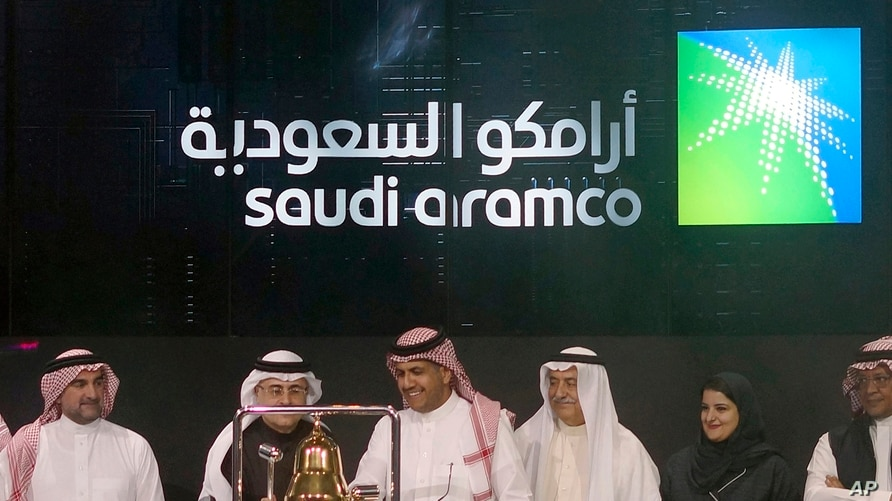 FILE - In this Dec. 11, 2019, file photo, Saudi Arabia's state-owned oil company Aramco and stock market officials celebrate…