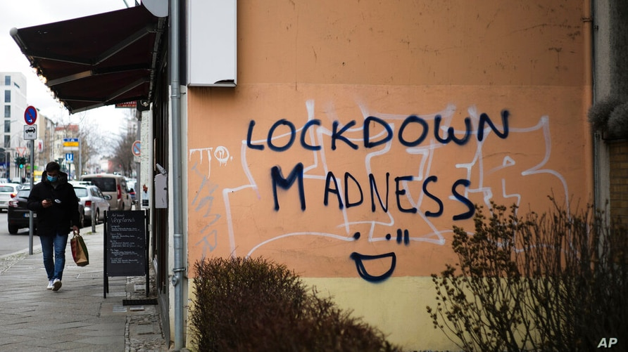 "A pedestrian walks by grafitti reading ""Lockdown Madness"" in the district Schoeneberg in Berlin, Germany, Tuesday, March 23,…"