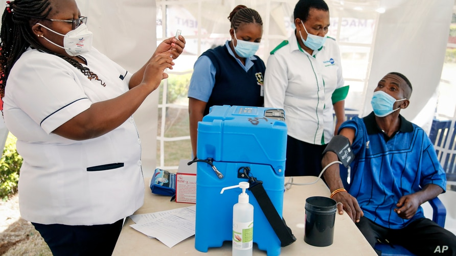 A nurse, left, prepares a shot of AstraZeneca COVID-19 vaccine, manufactured by the Serum Institute of India and provided through the global COVAX initiative, from a portable cold storage box, center, in Machakos, Kenya, March 24, 2021.