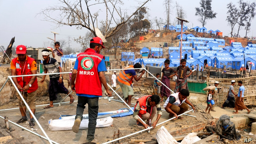 Authorities and volunteers from aid agencies rebuild shelters for Rohingya refugees who lost their dwellings to a devastating…