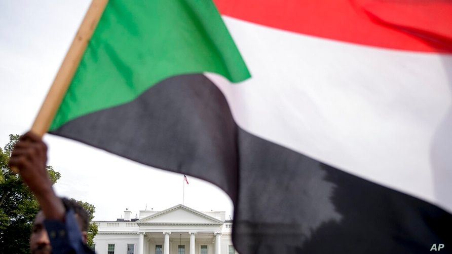 FILE - In this June 8, 2019 file photo, The White House is visible behind a man holding a Sudanese flag as Sudanese Americans…