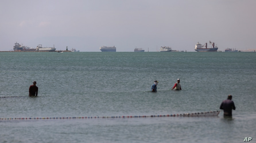 Cargo ships are seen in the Gulf of Suez as Ever Given, a Panama-flagged cargo ship that is wedged across the Suez Canal and blocking traffic, March 28, 2021.