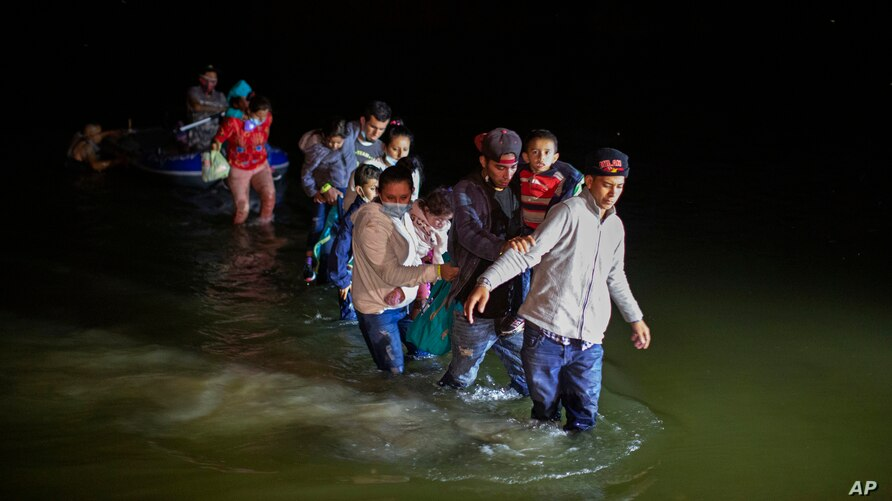 Migrant families, mostly from Central American countries, wade through shallow waters after being delivered by smugglers on small inflatable rafts on U.S. soil in Roma, Texas, March 24, 2021.