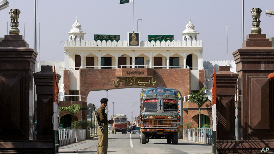 FILE - An Indian border security force soldier stands guard as an Indian truck, exporting goods to Pakistan, returns back towards the Indian side of joint check post between India and Pakistan at Wagah, India.