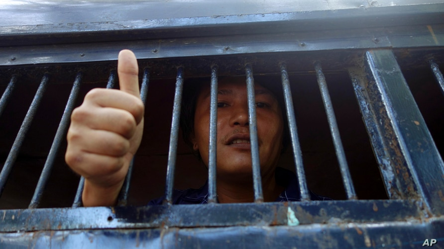 Moe Thway, one of the activists who protested against a controversial copper mine project, gives thumbs-up sign from police…