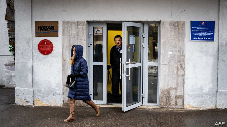 A security guard stands at the door of the building of the editorial office of Novaya Gazeta newspaper in Moscow, Russia, March 15, 2021.