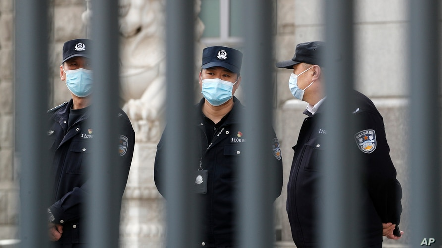 Policemen wearing face masks are seen at No. 2 Intermediate People's Court in Beijing, China, March 22, 2021.