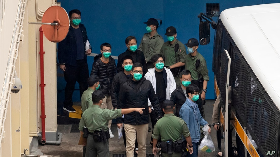 Some of the 47 pro-democracy activists including Lam Cheuk-ting, center, are escorted by Correctional Services officers to a prison van in Hong Kong, March 4, 2021.