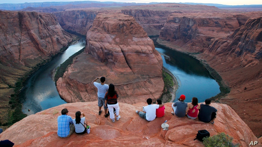 FILE - Visitors view the dramatic bend in the Colorado River at the popular Horseshoe Bend at the Glen Canyon National Recreation Area, in Page, Arizona, Sept. 9, 2011.