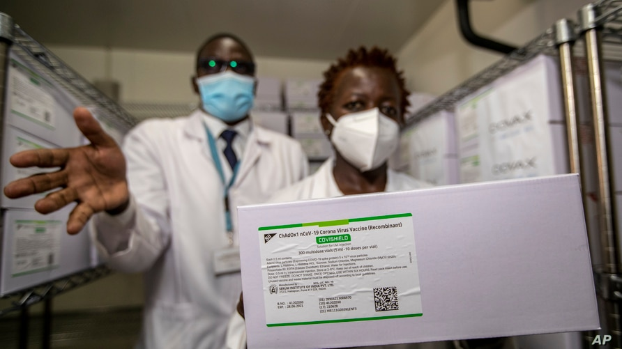 Technicians show a carton of AstraZeneca COVID-19 vaccine manufactured by the Serum Institute of India, inside a cold storage room at the central vaccine depot in Kitengela town on the outskirts of Nairobi, Kenya, March 4, 2021.