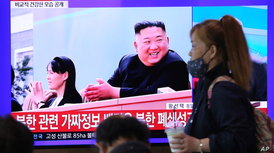 FILE - A woman passes by a TV screen showing an image of North Korean leader Kim Jong Un and his sister Kim Yo Jong during a news program, at the Seoul Railway Station in Seoul, South Korea, May 2, 2020.