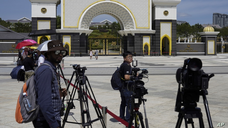 FILE - Journalists are seen gathered outside the National Palace, in Kuala Lumpur, Malaysia, Feb. 27, 2020.