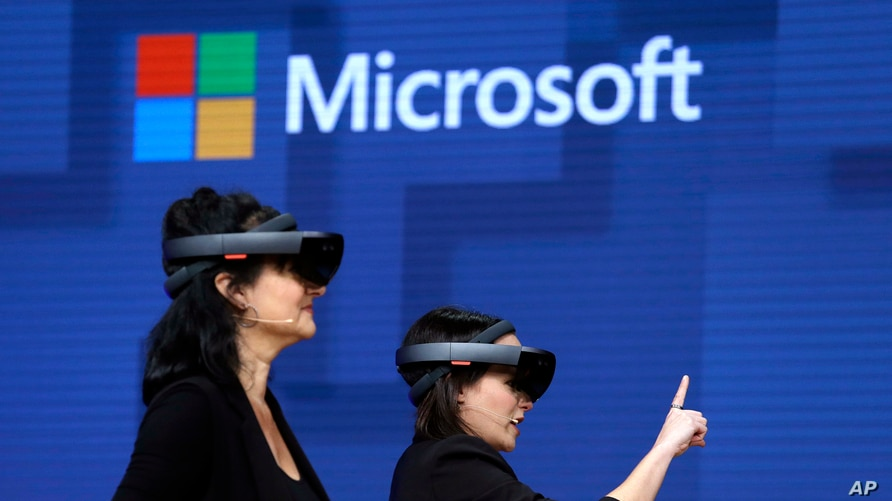 FILE - Members of a design team demonstrate the use of Microsoft's HoloLens device at a developers conference in Seattle, Washington, May 11, 2017. Microsoft says it has won a major contract to supply the U.S. Army with its virtual reality headsets.