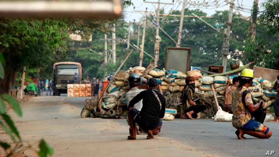Anti-coup protesters squat behind a barricade that separates them from security forces on the opposite side of the road, in the Dala township of Yangon, Myanmar, Mar. 26, 2021.
