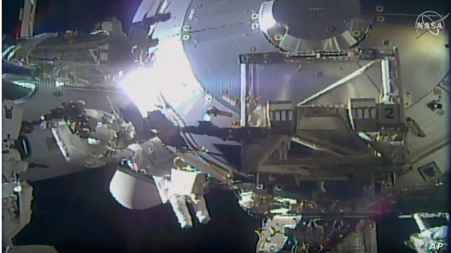 FILE - In this image taken from NASA video, astronauts perform routine maintenance on the International Space Station, Jan. 27, 2021.