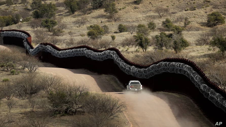 FILE - A Customs and Border Control agent patrols on the U.S. side of a razor-wire-covered border wall along the U.S.-Mexico border, east of Nogales, Arizona, March 2, 2019.
