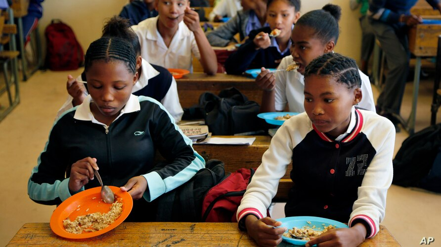 Students have a meal they received from a government sponsored feeding scheme at the Delta Primary School in Vosburg, South Africa, Nov. 14, 2019.