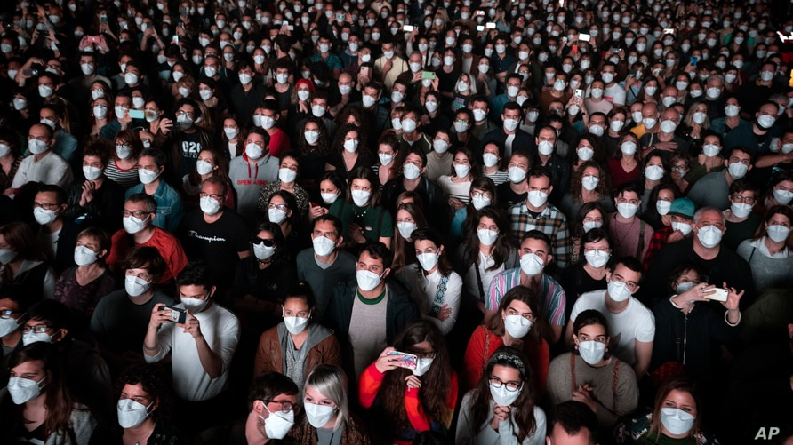People using face masks attend a music concert in Barcelona, Spain, March 27, 2021.