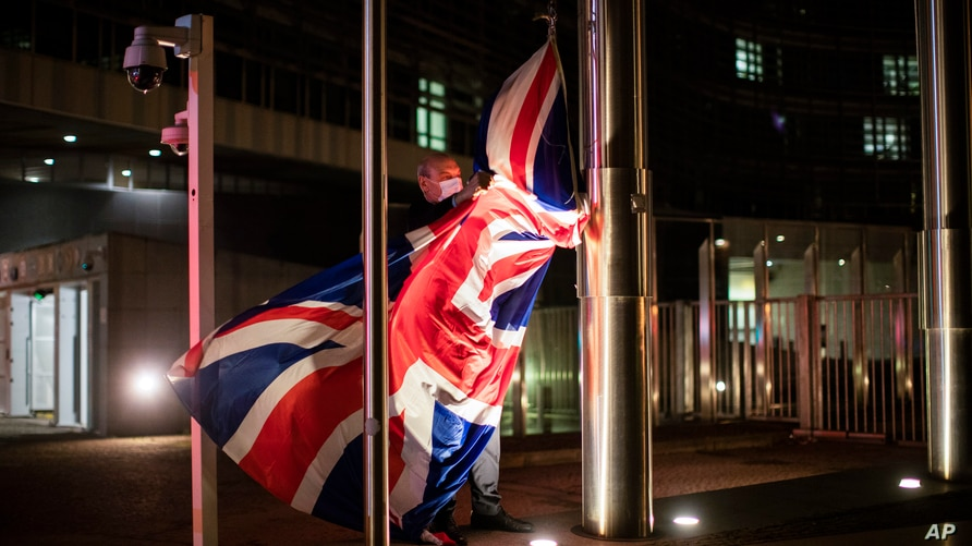FILE - A worker raises a British flag prior a meeting between European Commission President Ursula von der Leyen and British Prime Minister Boris Johnson at EU headquarters in Brussels, Belgium, Dec. 9, 2020.