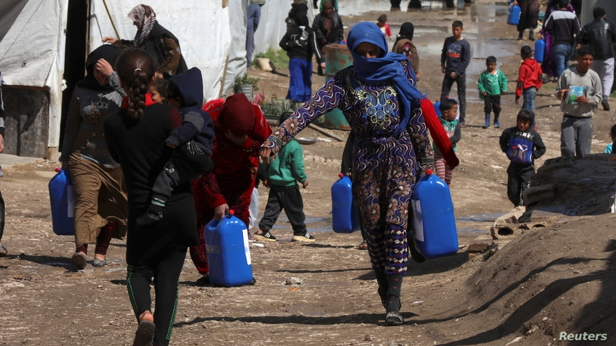 FILE - Syrian refugees walk as they carry containers at a tent settlement in Lebanon's Bekaa Valley, March 12, 2021.