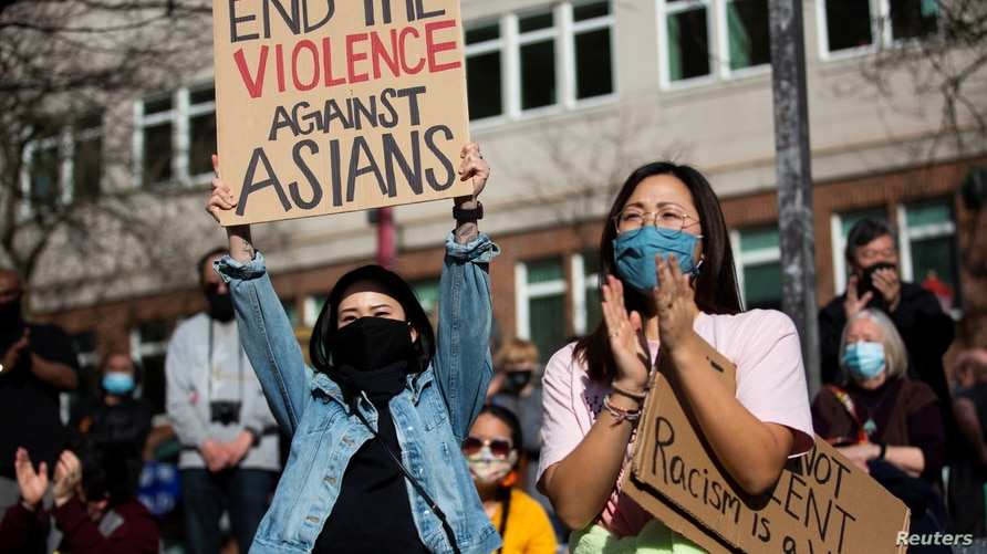 Dawn Cheung and Victoria Do clap and cheer while listening to speakers during a protest against anti-Asian hate crimes at Hing Hay Park in the Chinatown-International District of Seattle, Washington, March 13, 2021.