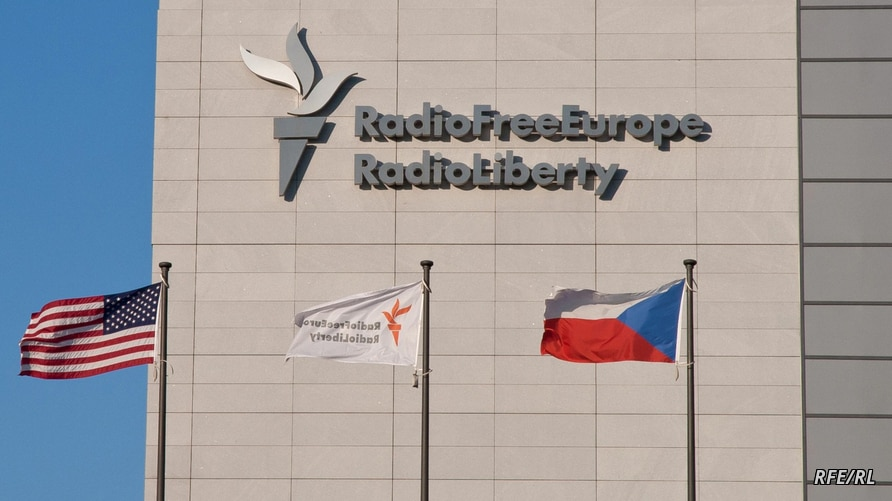 FILE - Signage is seen on the headquarters building of Radio Free Europe/Radio Liberty (RFE/RL), with the United States, RFE/RL and the Czech Republic's flags fluttering in the foreground, in Prague. (Jan Rambousek - RFE/RL)