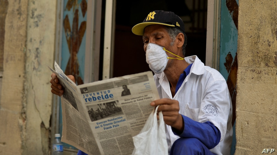 A man reads a newspaper as he wears a face mask in Havana, on March 12, 2020 as the world battles the outbreak of the new…