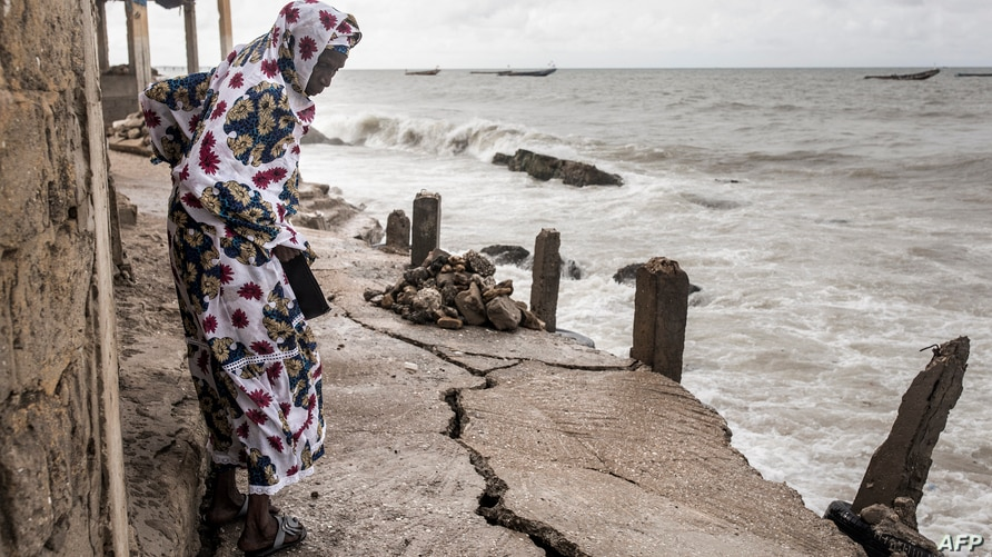 A woman looks down a newly formed crack in the walk way which leads to the Mosque in Bargny on September 18, 2020. - Fishing…