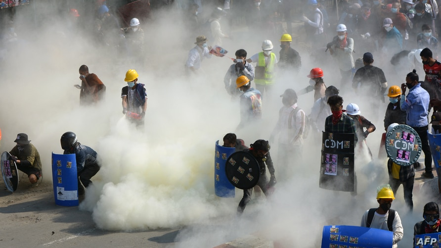 Protesters react after tear gas is fired by police during a demonstration against the military coup in the northwestern town of…