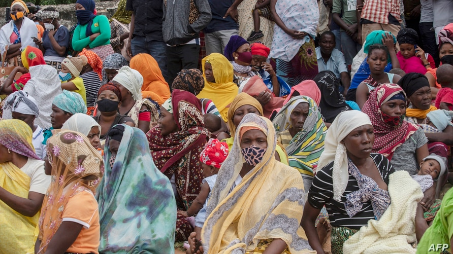 Families wait outside the port of Pemba on April 1, 2021, for the boat of evacuees from the coasts of Palma. - More than a…