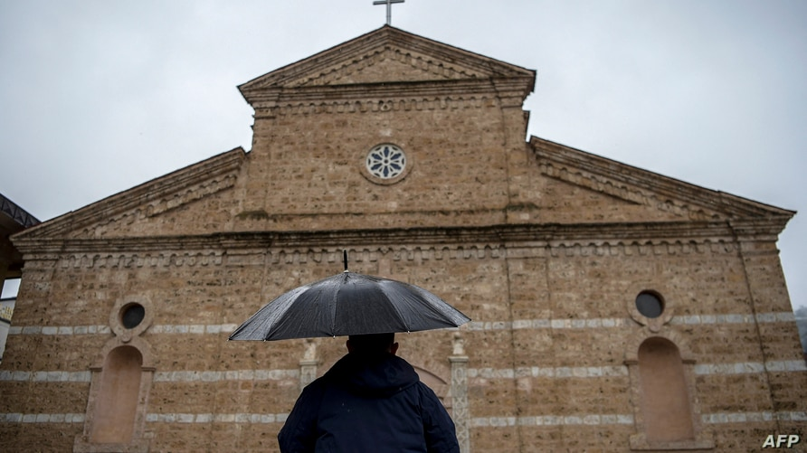A Catholic worshipper arrives for the Easter mass held at the Roman Catholic cathedral of the Lady Helper in the town of…