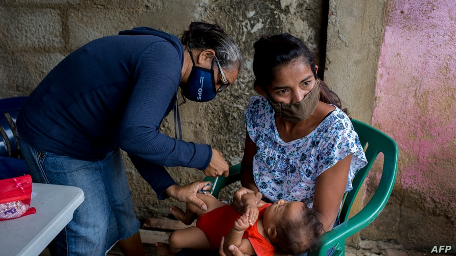 A child is vaccinated in Barcelona, Anzoategui State, Venezuela, on March 16, 2021. - In Venezuela there are people who had…