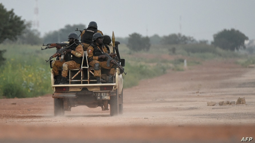 (FILES) In this file photograph taken on September 29, 2015, Burkinabe gendarmes patrol near the Presidential Security Regiment…