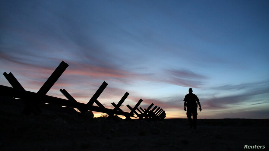 U.S. border patrol agent Alessio Faccin walks along the border fence separating Mexico from the United States near Calexico,…
