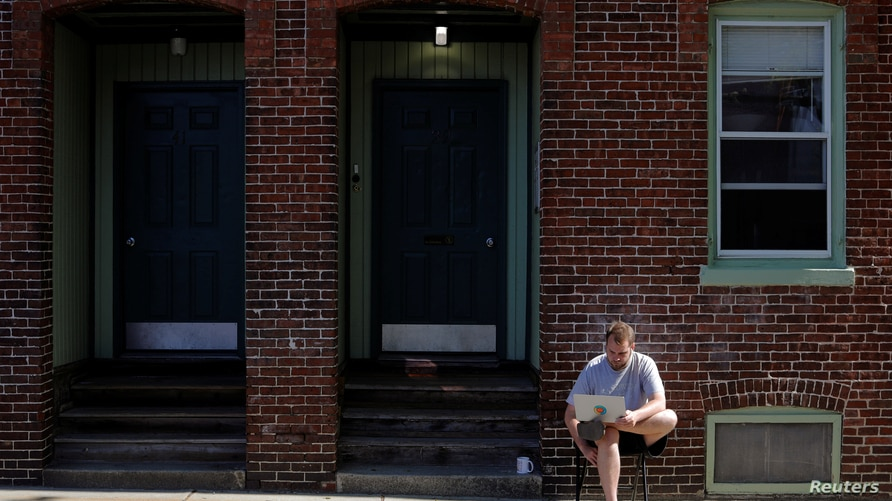 Jack Coopersmith sits outside his apartment and takes part in remote meeting while working from home amid the coronavirus disease (COVID-19) outbreak in Cambridge, Massachusetts,May 22, 2020.