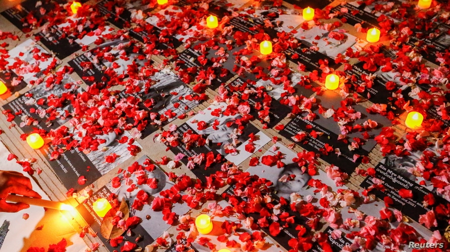 Flowers are seen near photos of protesters who died during a protest against the military coup Myanmar, outside the ASEAN…