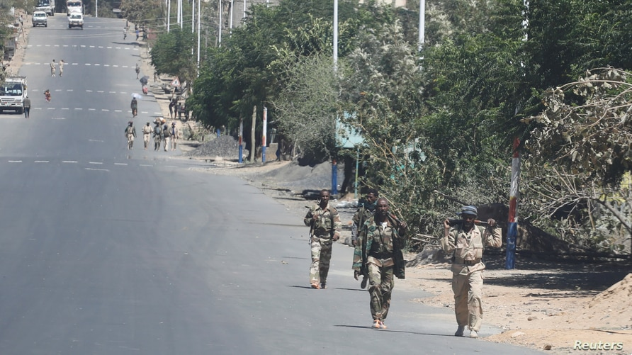 FILE PHOTO: Troops in Eritrean uniforms walk in the town of Bizet, Ethiopia, March 14, 2021.Picture taken March 14, 2021…